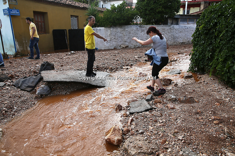 Pictured: People jump over a flooded road in the Magoula area, in the outskirts of Athens, Greece. Wednesday 27 June 2018<br /> Re: Flashflooding has been caused by storm Nefeli in parts of Greece.