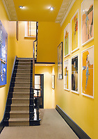A vibrant yellow hallway with ceiling spotlights is the perfect background for a display of modern art.