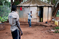 Ivan Matovu,13, practices baseball with his coach Okello Benard in front of his home at Kyambogo University sports ground, Uganda on July 28 2011. Ivan is the starting pitcher for Rev. John Foundation Little League baseball team.