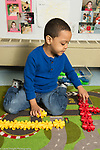 Education preschool 4-5 year olds boy counting manipulative connecting plastic toy pieces he has sorted by color
