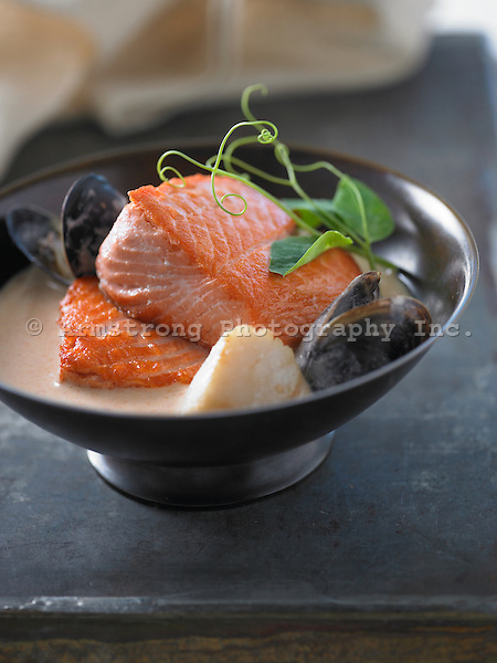 Large pieces of salmon in seafood broth, with mussels, scallops, and pea shoots.