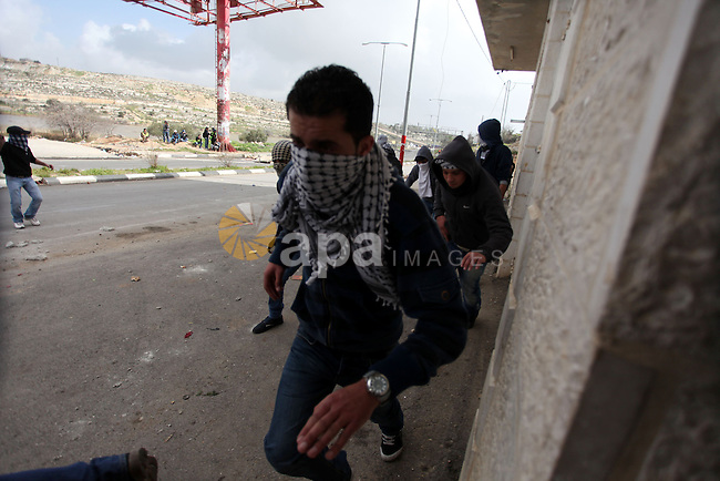 Palestinian protesters take cover during clashes next to the Israeli military prison 'Ofer' in Beitunya, south of the West Bank city of Ramallah, on February 24, 2013 following the death of a Palestinian prisoner held in Israel. Some 3,000 Palestinians held in Israeli jails were staging a one-day hunger strike in protest at the death of the inmate Arafat Jaradat, an official said, as security forces clashed with demonstrators in the West Bank. Photo by Issam Rimawi