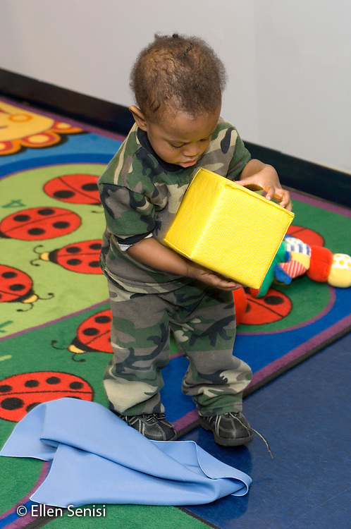 MR / Schenectady, NY.Schenectady Day Nursery / private non-profit daycare center / Infant class.Toddler (boy, 1, African-American / Hispanic) exploring object properties of yellow cube block with his hands..MR: Leo4 .© Ellen B. Senisi