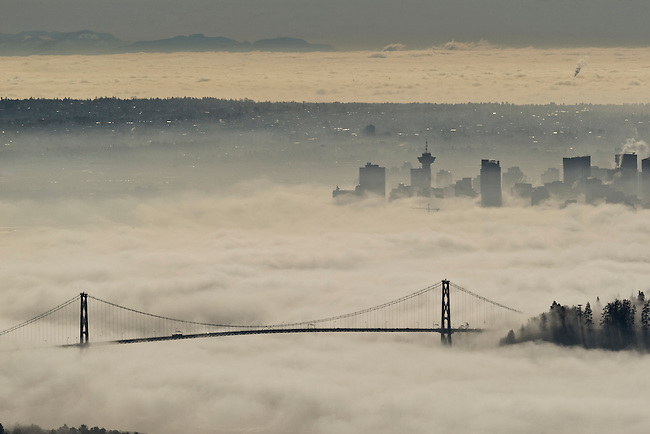 Low-lying fog covers the city of Vancouver, British Columbia.  This weather condition is called a temperature inversion, where the air closest to the ground is colder than the air at higher altitude; this can cause fog to form at ground level with clear skies above.  Photo By Gus Curtis.