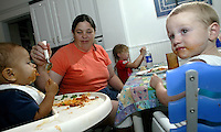 Foster parent Bobbi Pedersen, center left, feeds her foster child Kareem Craycraft, left, as her other foster child Christopher Gray, right, and adopted daughter Aleah Pederson enjoy their dinner Monday June 16, 2003 in Columbus, Ohio.<br />