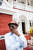 JAMAICA, Port Antonio. Albert Minott, lead singer of the Jolly Boys standing in front of a historicall building.