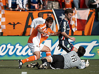 Houston Dynamo defender Eddie Robinson (left) helps Dynamo goalkeeper Pat Onstad (18) save a goal as New England Revolution forward Pat Noonan follows through.  The Houston Dynamo win MLS Cup 2006 over the New England Revolution 4-3 on penalty kicks after playing to a 1-1 tie during regulation and extra time at Pizza Hut Park in Frisco, TX on November 12, 2006.