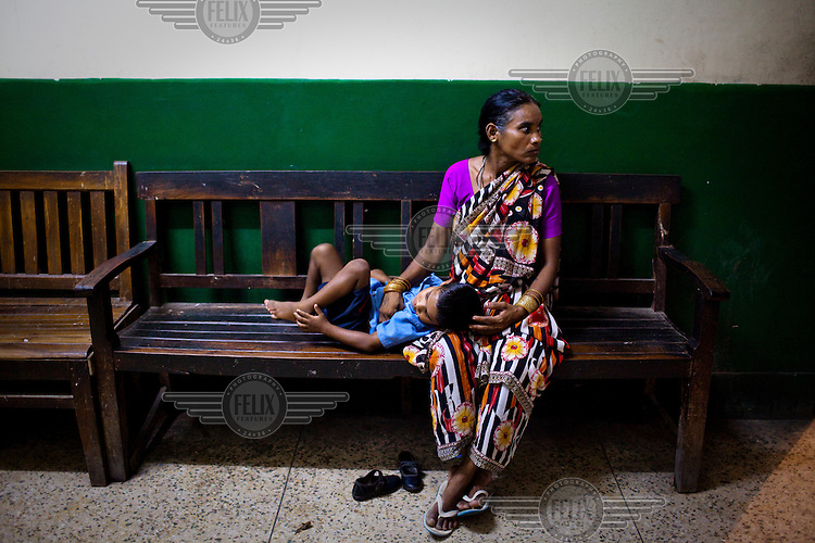 A woman waits with her child outside the doctor's clinic  at Maharani Laxmibai Medical College in Jhansi.