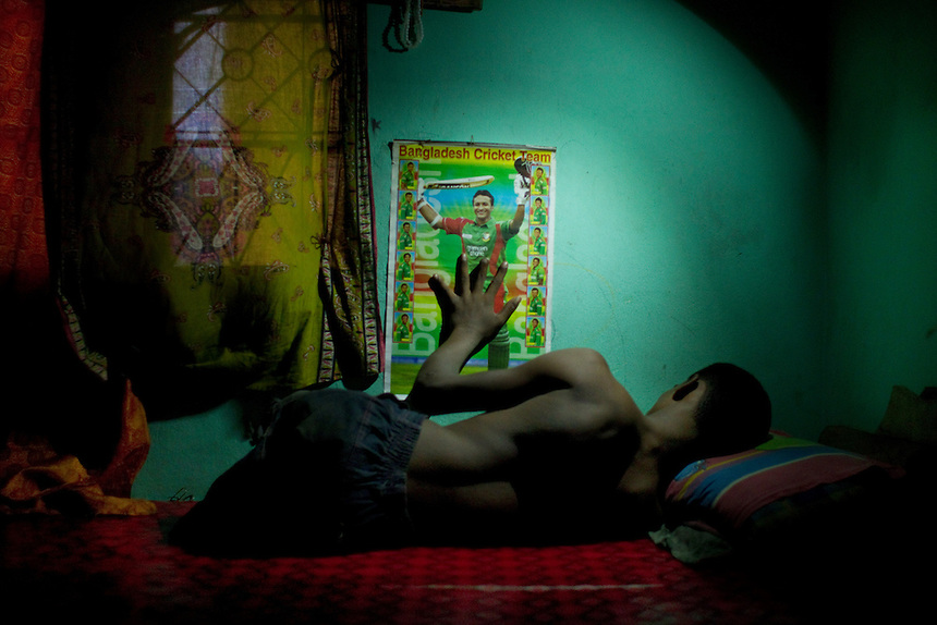 Mohammad Sharif lies on the bed in his bedroom in Chittagong, Bangladesh.