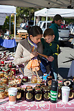 USA, Oregon, Ashland, a woman and her son taste Jam at the Pennington Farms booth, the Rogue Valley Growers and Crafters Market