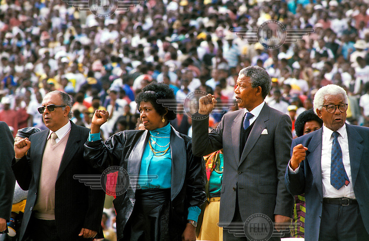 From left to right: Ahmed Kathrada, Winnie Mandela, Nelson Mandela and Walter Sisulu at a welcome rally at the FNB stadium in Soweto after the release of Nelson Mandela from prison.