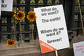 A placard which says 'What do we want? The Earth! When do we want it? Forever!' leans against the railings in front of the Houses of Parliament with four sunflowers during the Climate Change demonstration, London, 21st September 2014. © Sue Cunningham