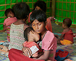 One day after they made the perilous crossing from Myanmar into Bangladesh, weary 9-year old Ruzi holds her sleeping 2-year old sister Jainuray in a United Nations clinic for severely malnourished Rohingya children in the Balukhali Refugee Camp near Cox's Bazar, Bangladesh. She has been feeding her Plumpy'nut, a peanut-based supplement given to malnourished children. <br /> <br /> More than 600,000 Rohingya have fled government-sanctioned violence in Myanmar for safety in Bangladesh.