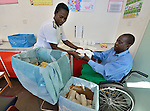 Sunny Nyamandwe (right) folds and packages bandages as part of his work at the National Rehabilitation Centre in Ruwa, Zimbabwe. The Centre assembles and fits wheelchairs provided by the Jairos Jiri Association with support from CBM-US, and Nyamandwe is one of the beneficiaries of the program. His legs remain paralyzed after an automobile accident more than two decades ago.