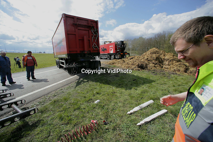 Foto: VidiPhoto..APELDOORN - Op knooppunt Beekbergen (A1/A50) is zaterdagmiddag een vrachtwagen met droge mest voor de champignonteeld gekanteld. De combinatie kantelde in een bocht van de afrit A1 richting Arnhem. Het overige verkeer werd enkele uren omgeleid. De oorzaak van het ongeval is niet bekend. De chauffeur (l.) bleef ongedeerd.