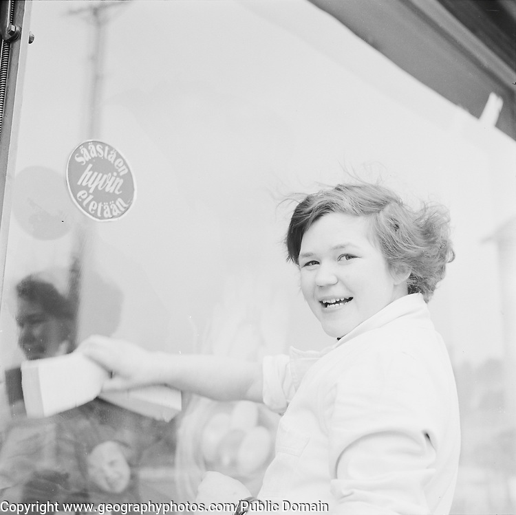 Female worker washing shop window, Finland 1960s