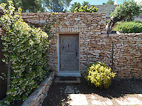 A studded garden door leads through one of the dry-stone walls into another part of the grounds