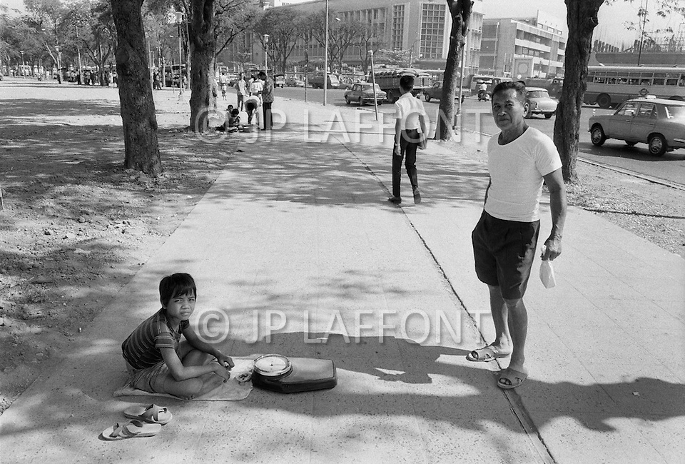 A child is employed to weight people with a scale in the streets in Bangkok, Thailand  - Child labor as seen around the world between 1979 and 1980 – Photographer Jean Pierre Laffont, touched by the suffering of child workers, chronicled their plight in 12 countries over the course of one year.  Laffont was awarded The World Press Award and Madeline Ross Award among many others for his work.