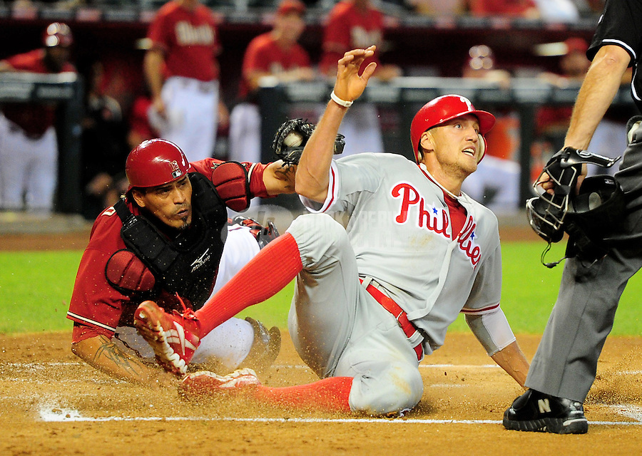 Apr. 25, 2012; Phoenix, AZ, USA; Philadelphia Phillies base runner Hunter Pence (right) is tagged out at the plate by Arizona Diamondbacks catcher Henry Blanco in the first inning at Chase Field. Mandatory Credit: Mark J. Rebilas-