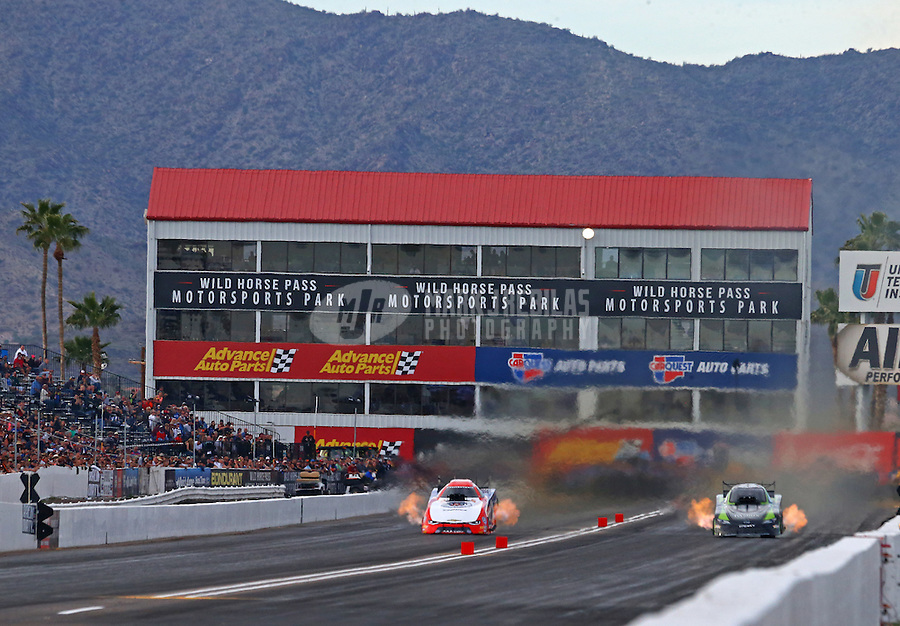 Feb 25, 2017; Chandler, AZ, USA; NHRA funny car driver Robert Hight (left) races alongside Alexis DeJoria during qualifying for the Arizona Nationals at Wild Horse Pass Motorsports Park. Mandatory Credit: Mark J. Rebilas-USA TODAY Sports