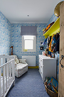 The nursery is decorated with a blue and white theme with patterned wallpaper and carpeting. The room is furnished with a cot and a chest of drawers.
