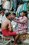 Getting a shave at market, Kolkata, India