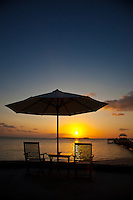 Sunset, Deck Chairs and Sun Umbrella on the beach at Wakatobi Dive Resort, Southeast Sulawesi, Indonesia.