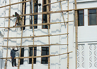 workers painting a budiling on bamboo-construction,  Yogyakarta, island Java, archipelago of Indonesia,  September 2011