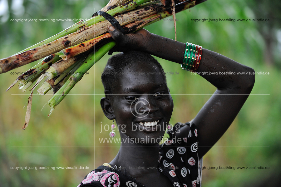 SOUTH SUDAN  Bahr al Ghazal region , Lakes State, town Rumbek , portrait of Dinka woman, carrying sugarcane