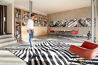 A woman moves through a spacious contemporary room with a concrete floor walls. The room is sparsely furnished with classic Eames chairs, a simple table and a shelving and cupboard unit.