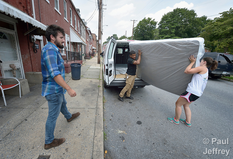 Luis Ortiz and Emilie MacDonald carry a mattress as Josh Digrugilliers looks on as the three furnish what will become home for a refugee family about to arrive in the United States. They work for Church World Service, which resettles refugees in Pennsylvania and other locations in the United States. <br /> <br /> Photo by Paul Jeffrey for Church World Service.