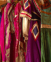 A row of jewel-coloured costumes, their vivid shades and geometric patterns still glowing despite the fraying and tarnished gold embellishments
