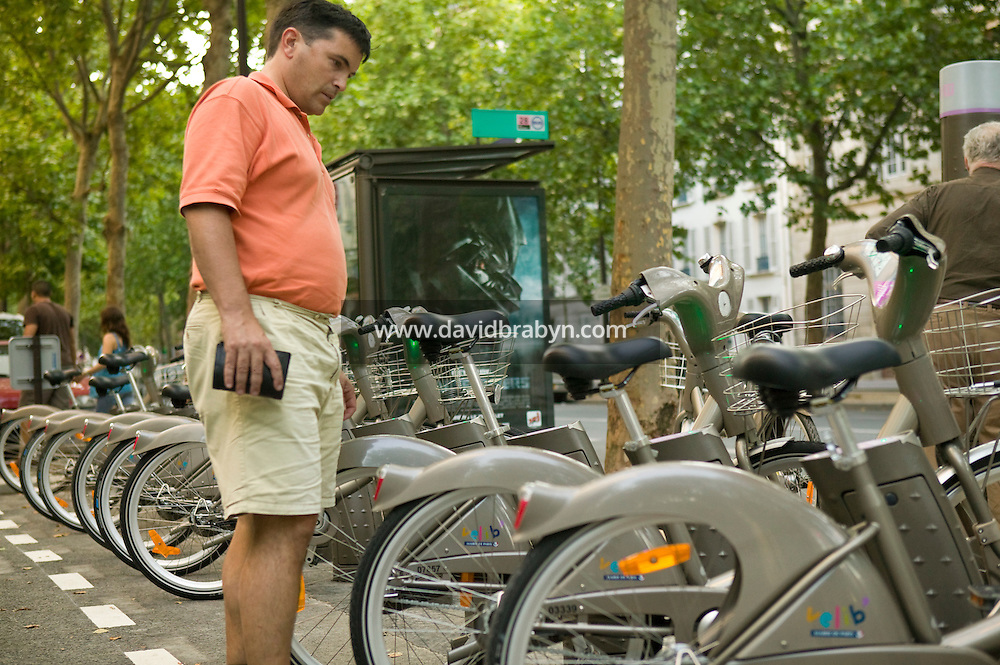 A man examines Velib' bicycles standing at a docking station in Paris, France, 15th July 2007. The city of Paris launched this low-cost self-service bicycle system today with a fleet of 10,000 bicycles.