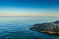 Klippa vid ett lugnt och stilla hav på Nåttarö i Stockholms skärgård. / Cliff at a calm and quiet sea on Nåttarö in the Stockholm archipelago Sweden.