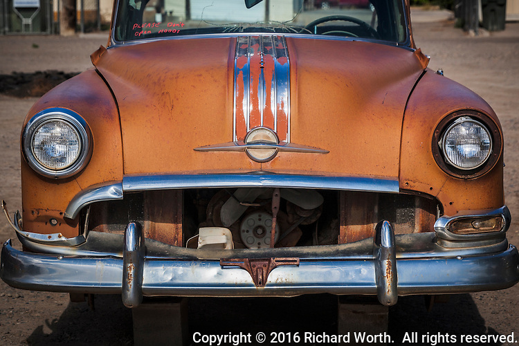 An old Pontiac, minus its grill, offers a toothless 'Hello', from a lot along a small town mainstreet.