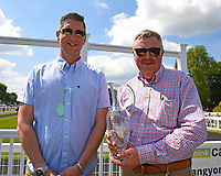 Trainer of Edged Out Christopher Mason right receives his trophy for winning The Think Cars Ssangyong Paddock Area Display Handicap,co during Father's Day Racing at Salisbury Racecourse on 18th June 2017