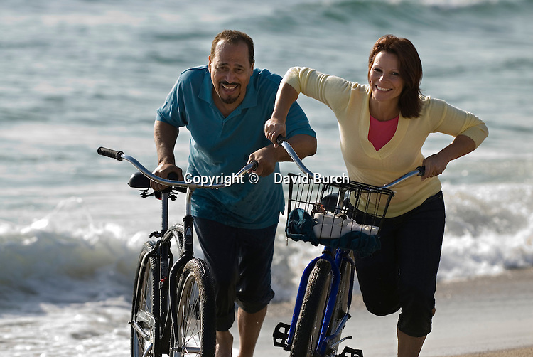 Mature couple running with bicycles at beach, smiling
