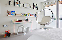 An Eero Aarnio bubble chair hanging from the ceiling is a fun feature in a teenager's bedroom. A low secret door leads to a sibling's bedroom beyond.
