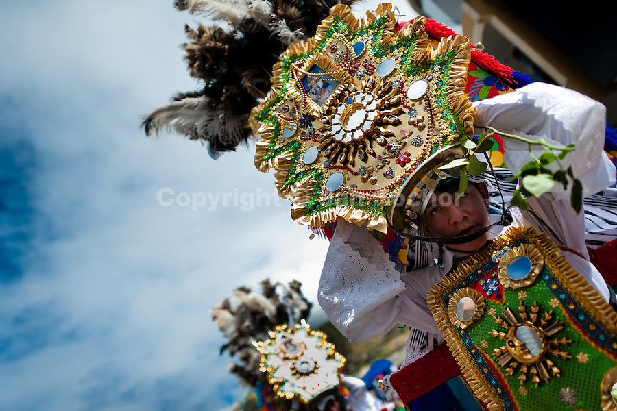 A young dancer (danzante) performs in the religious parade within the Corpus Christi festival in Pujilí, Ecuador, 10 June 2012. Every year in June, thousands of people gather in a small town of Pujili, high in the Andes, to celebrate the Catholic feast of Corpus Christi. Introduced originally during the Spanish conquest of South America, this celebration merges Catholic rituals of Holy Communion with the traditional Andean harvest and sun festivities (Inti, the Inca sun god). Women dancers perform wearing brightly colored costumes while men dancers wear chest ornaments and heavy elaborate headdresses adorned with mirrors, jewelry, or natural items (shells). Being a dancer in the Corpus Christi ceremonial parade (El Danzante) is considered an honour and a privilege by the indigenous people in Ecuador.