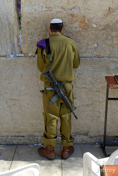 An Israeli soldier prays at the Western Wall, all that remains of the first and second temples. The Wall is located in East Jerusalem, annexed illegally by Israel in 1967.