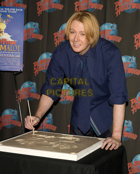 "CLAY AIKEN .Handprint ceremony in celebration for starring role in ""Monty Python's Spamalot"" at Planet Hollywood Times Square, New York, NY, USA, .April 8, 2008..half length blue shirt tie autographing signing .CAP/LNC/TOM.©LNC/Capital Pictures"