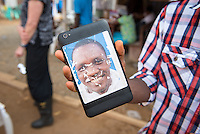 Not all portraits made it to their PPE. Hygienist Emmanuel Nagbe displays his image, which he placed on the back of his electronic device, at the ELWA II ETU (Ebola treatment unit) in Monrovia, Liberia on Tuesday, March 3, 2015. Occidental College professor Mary Beth Heffernan's PPE Portrait Project involves creating wearable portraits of health care workers who must wear PPE when caring for patients. <br /> (Photo by Marc Campos, Occidental College Photographer) Mary Beth Heffernan, professor of art and art history at Occidental College, works in Monrovia the capital of Liberia, Africa in 2015. Professor Heffernan was there to work on her PPE (personal protective equipment) Portrait Project, which helps health care workers and patients fighting the Ebola virus disease in West Africa.<br />