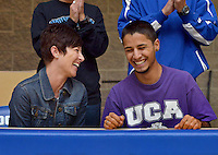 STAFF PHOTO BEN GOFF  @NWABenGoff -- 12/05/14 Austin Salazar shares a laugh with his mother Emily Salazar after signing a national letter of intent to run track and cross country at the University of Central Arkansas during a ceremony in the commons at Rogers High on Friday Dec. 5, 2014.