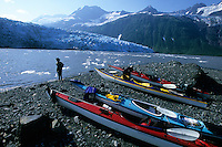 A sea kayaker enjoys Harriman Glacier and the surrounding Chugach Mountains in Prince William Sound's Harriman Fjord, north of Whittier, Alaska.