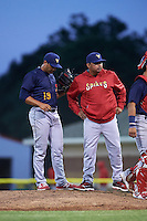 State College Spikes pitching coach Darwin Marrero (39) turns to the dugout after talking with pitcher Steven Farinaro (19) during a game against the Batavia Muckdogs on June 24, 2016 at Dwyer Stadium in Batavia, New York.  State College defeated Batavia 10-3.  (Mike Janes/Four Seam Images)
