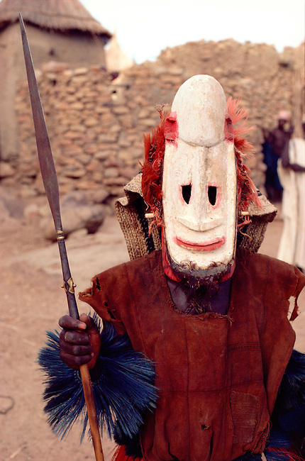 Dogon masked dancer, in character of Fulani warrior with his spear to frighten imaginary rustlers, at ceremonial dance. Tireli. Mali. West Africa.