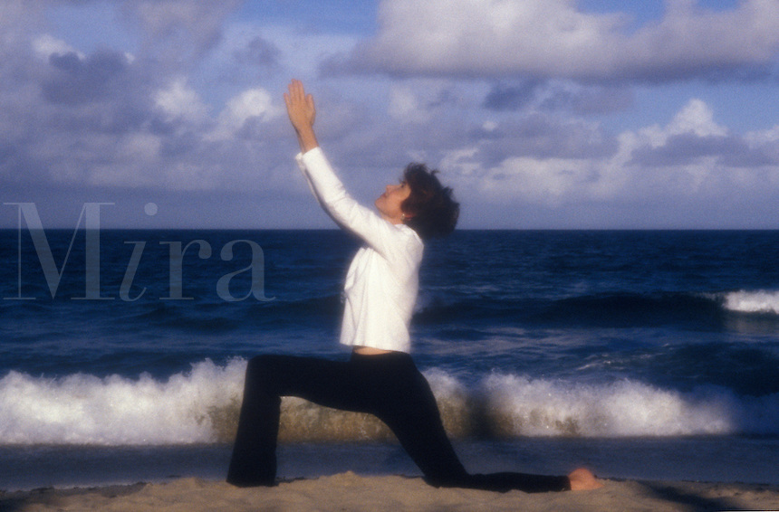Woman practicing yoga on the beach.