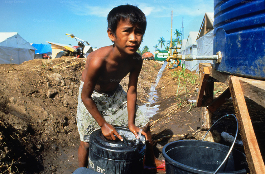 VOLCANO AFTERMATH, Philippines. Boy collecting water in refugee camp. Central Luzon, Mount Pinatubo volcano erupted in 1991  and caused massive destruction of urban and rural landscape. Many indigenous  Aeta and Igorot people were displaced. White volcanic  ashes settled and disfigured the landscape.   Many  live in ramshackle shelters, in  refugee camps and settlements, living on humanitarian aid.