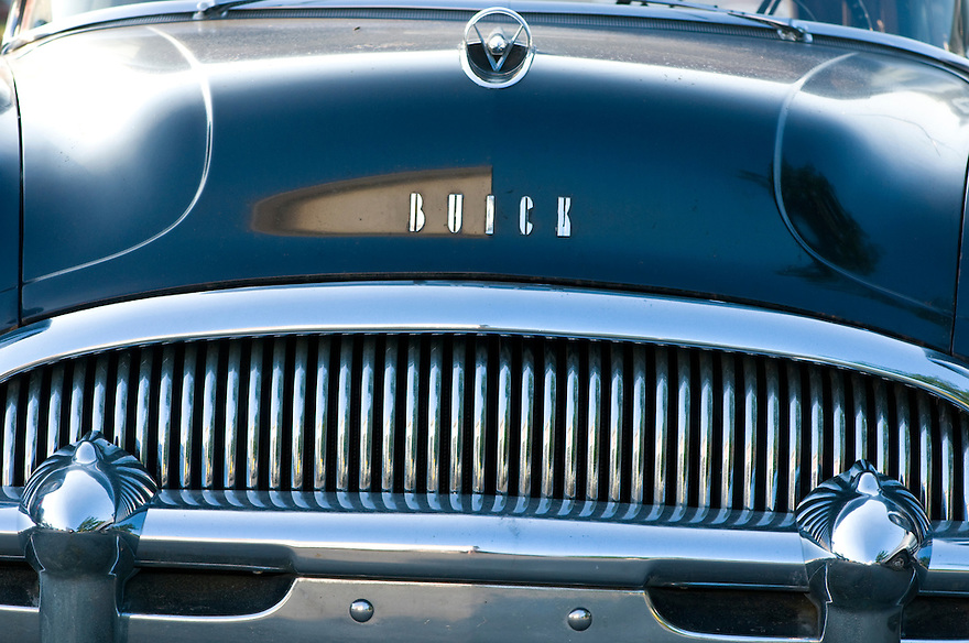 Luxury, Simplicity, Mode of Transport, Symbol, Shiny, History, Nostalgia, Technology, Transportation, Land Vehicle, Vertical, Extreme Close Up, Close-up, Side View, Design, 1950s Style, 1960s Style, Restoring, USA, Car, Descriptive Color, Blue, Pattern, Old, Old-fashioned, Metal, Sedan, Traditional Culture, American Culture, Light, Aging Process, Buick, Art Product, Art, Color Image, Chrome, Silver, Front view, Antique, Photography, Fashion, Retro Revival, Motor Vehicle.