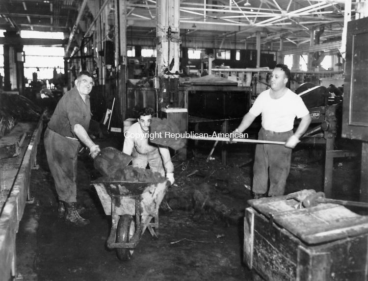 Employees at American Brass in Waterbury shovel mud and debris off the plant floor following Connecticut's 1955 flood.